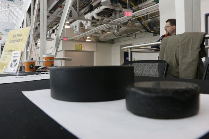 A standard hockey puck (right) besides a modified puck (left) that blind hockey players play with. Photo: Luke Galati