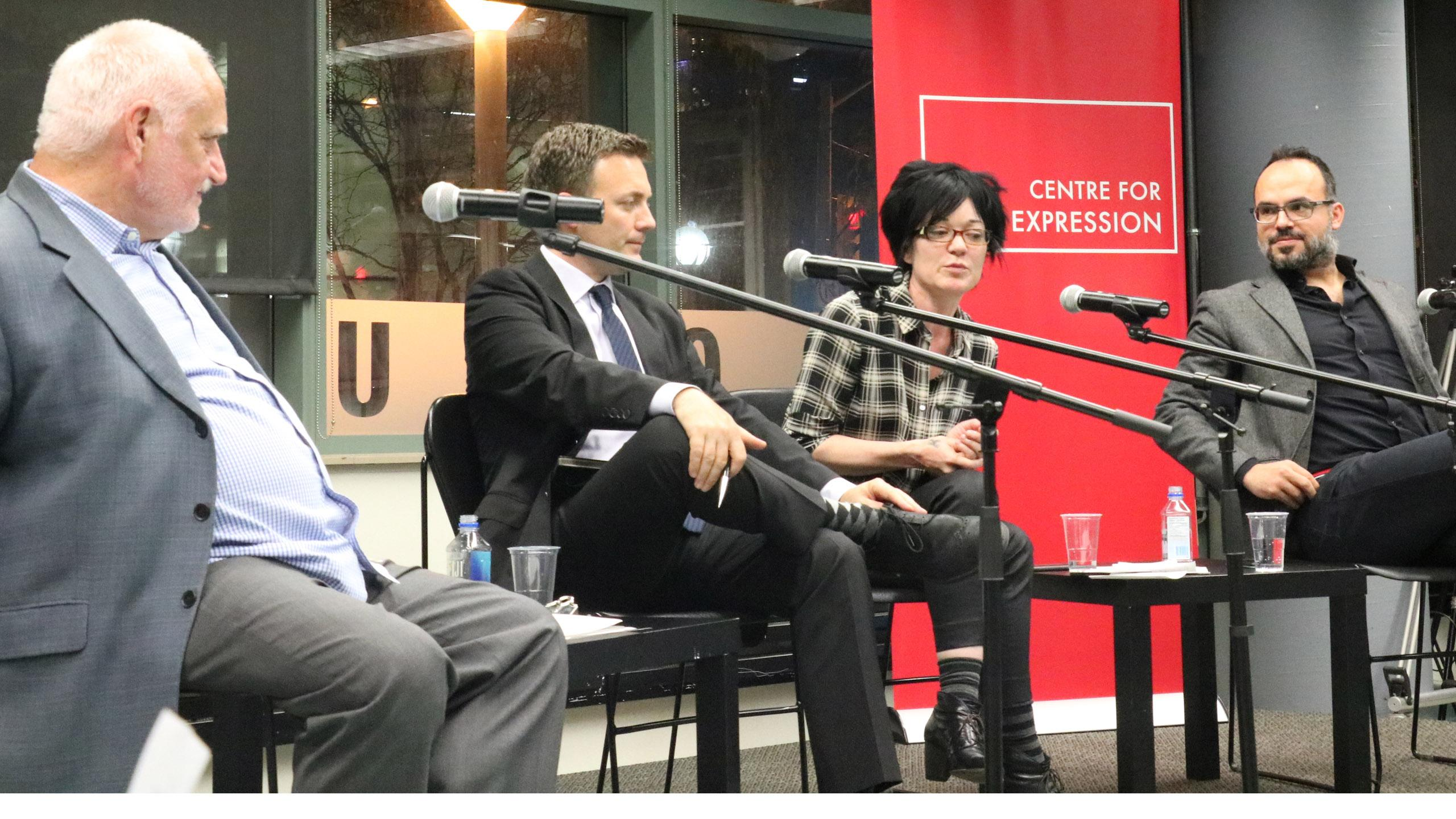 The panel sits in front of a window and speaks into microphones.