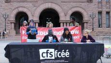 three CFS members sit at a table in front of city hall reading demands