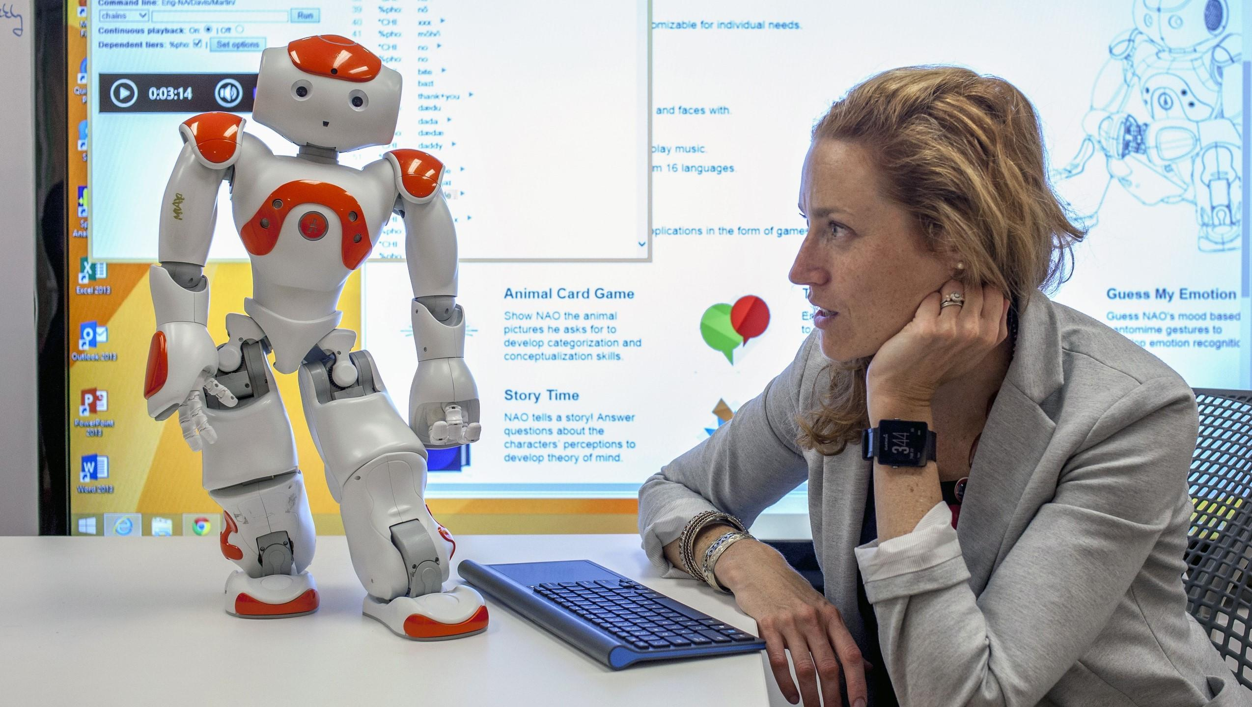 Stephanie Walsh Matthews sits with Max the robot.