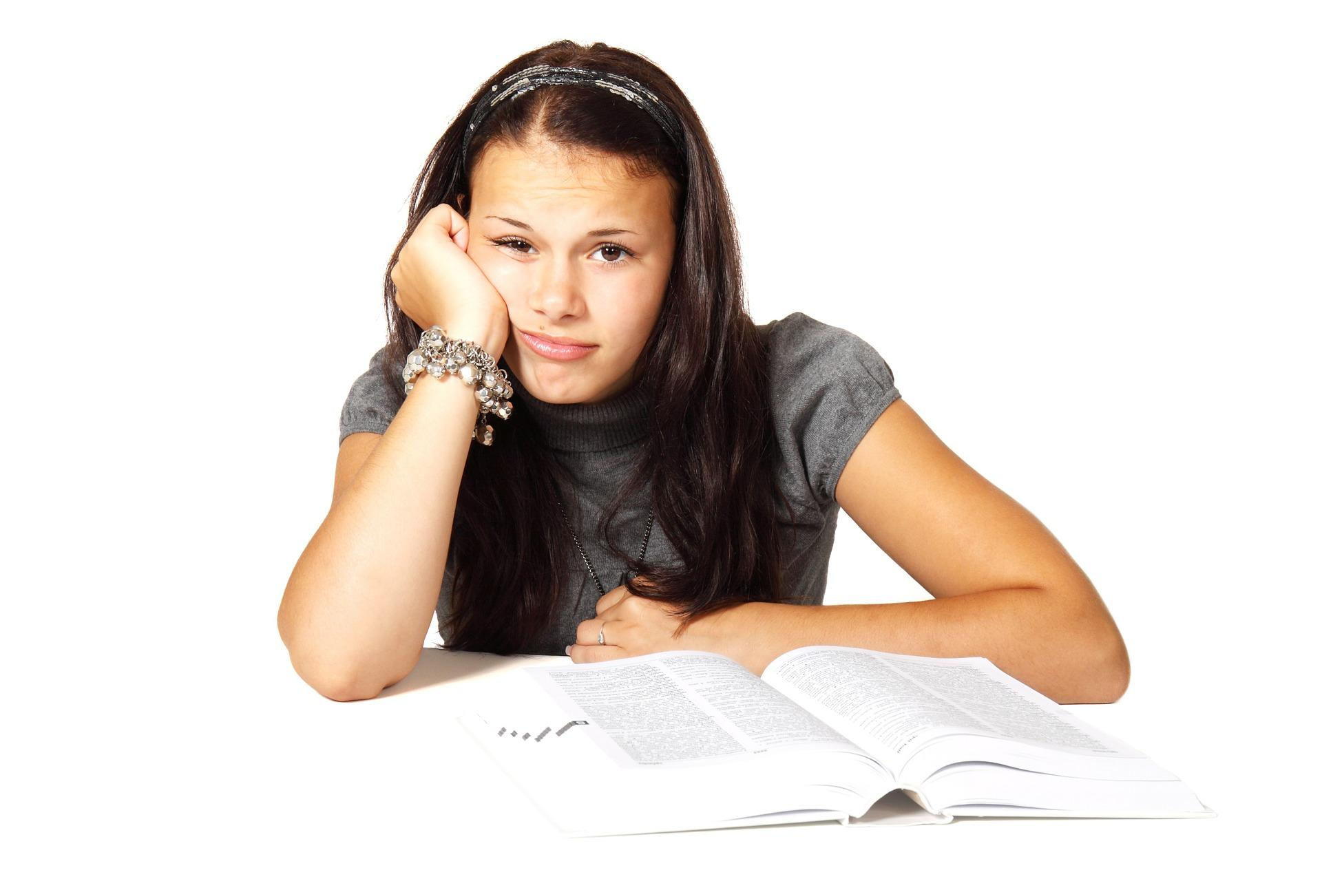 A woman reading a textbook rests her head on her hand.