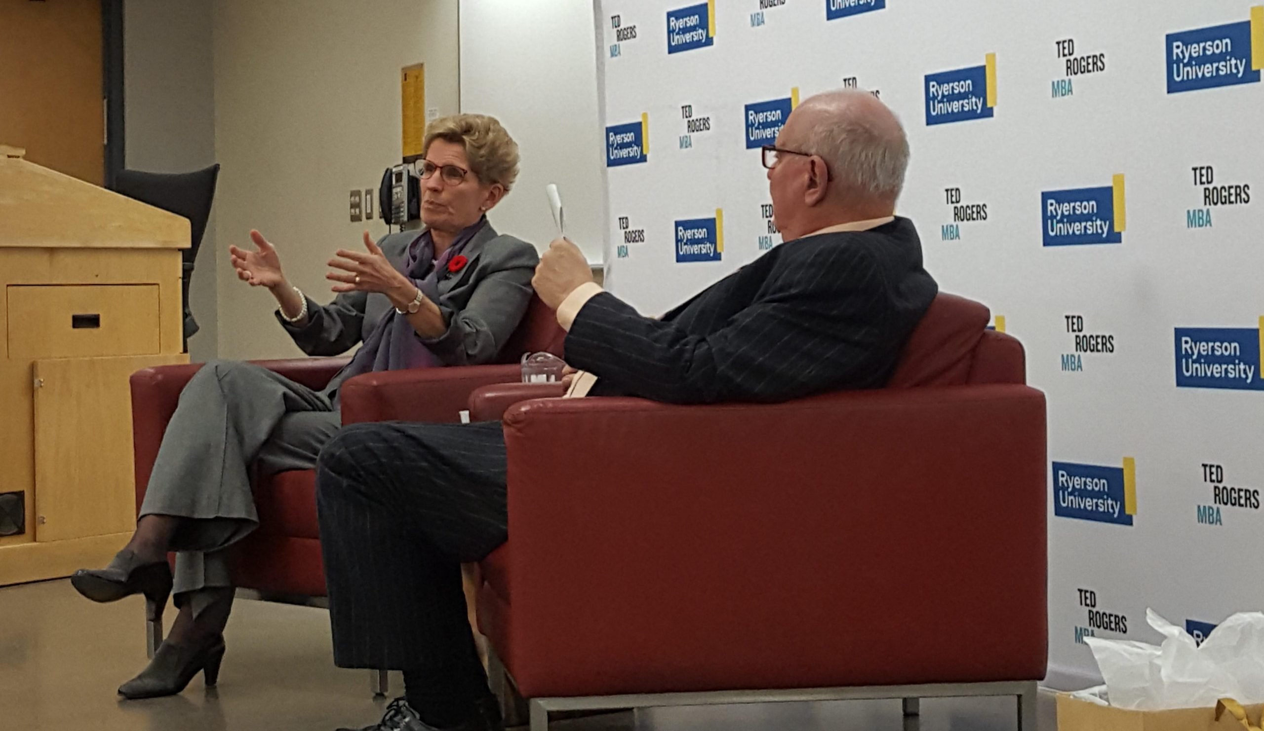 Kathleen Wynne sits in a chair next to Ralph Lean