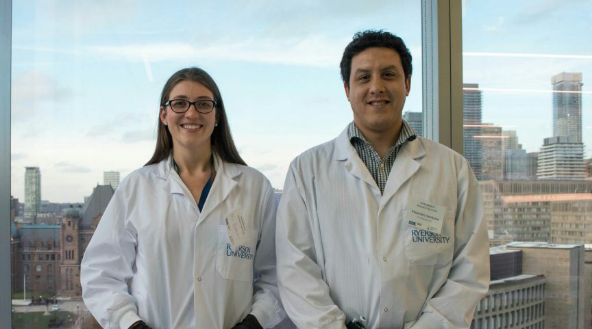 Aly Burtch and Alejandro Saettone wear lab coats and stand side-by-side in front of a window.