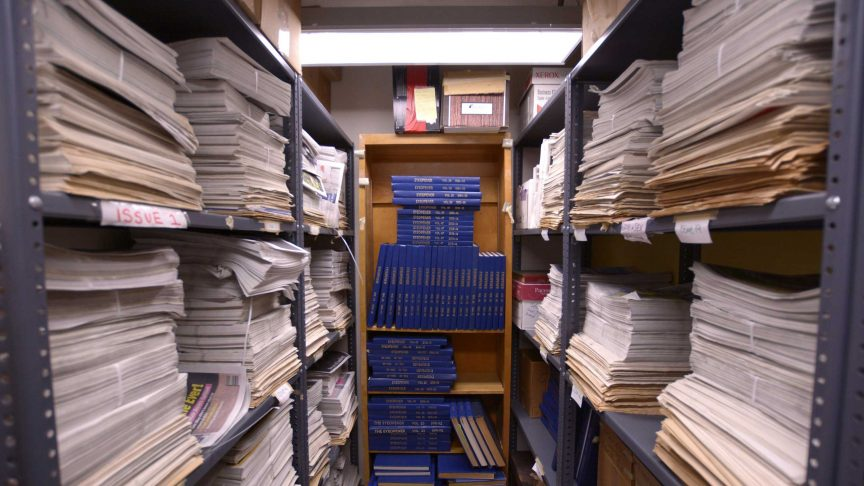 "A look inside small room lined with floor to ceiling shelves, full of large stacks of newspapers. At the back of the room is a shelf with blue books labelled as ""Eyeopener"" with different dates. The room is poorly lit but cozy."