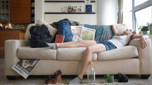 A girl laying on a couch surrounded by her travel items.