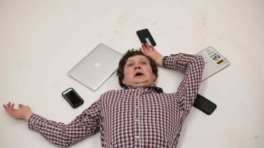 A man lies on the grown looking scared and confused. He is surrounded by phones and laptops.