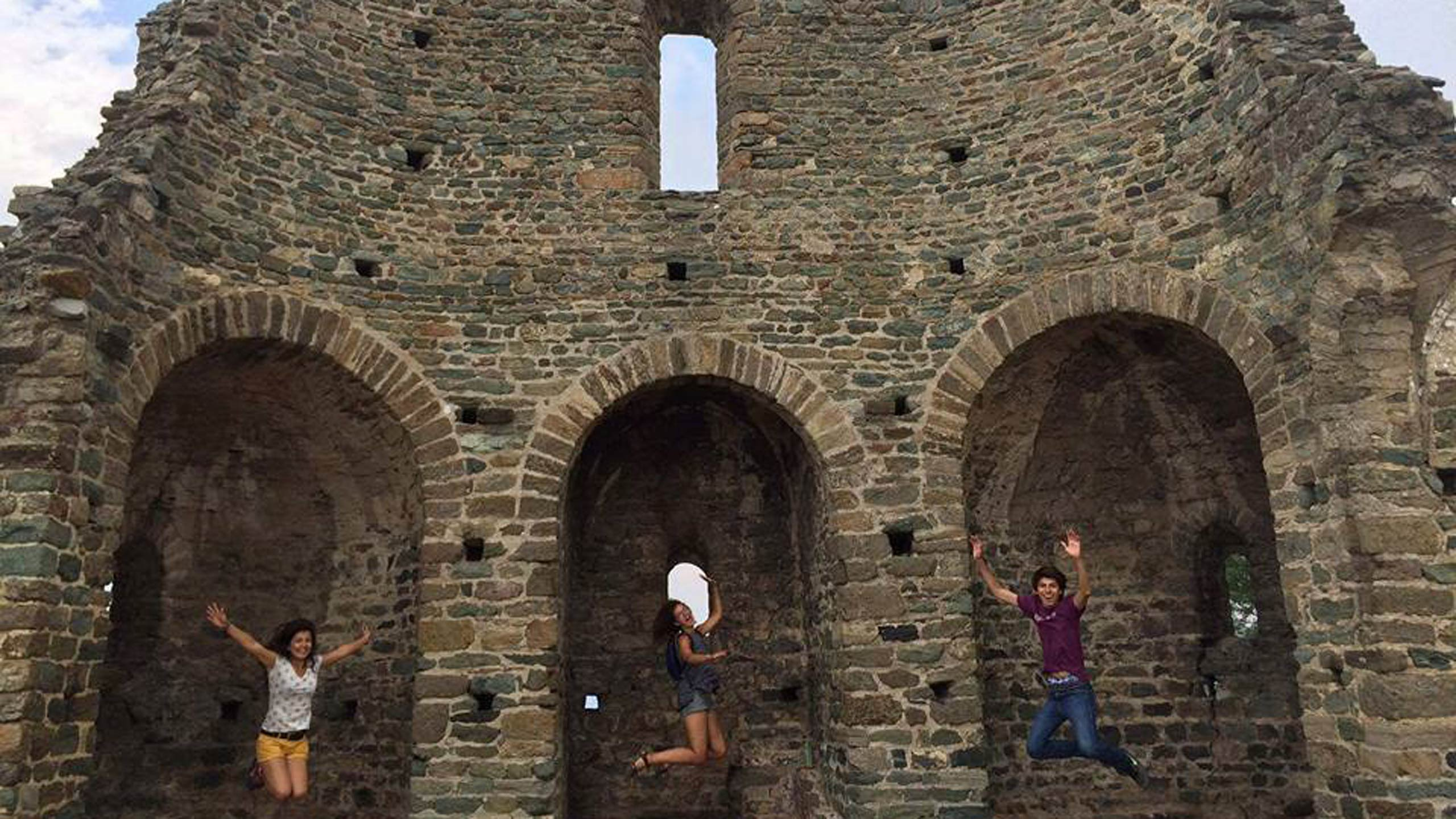Three people jumping in the air in front of an old stone building