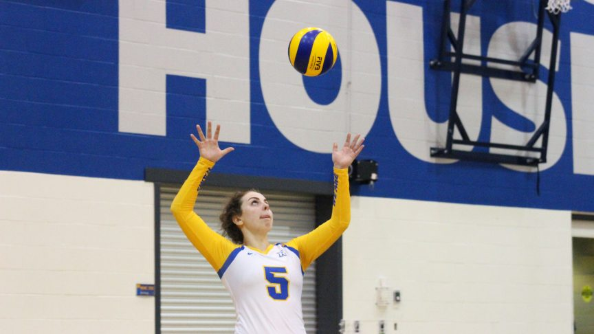 Volley ball player number 5 goes up for a serve