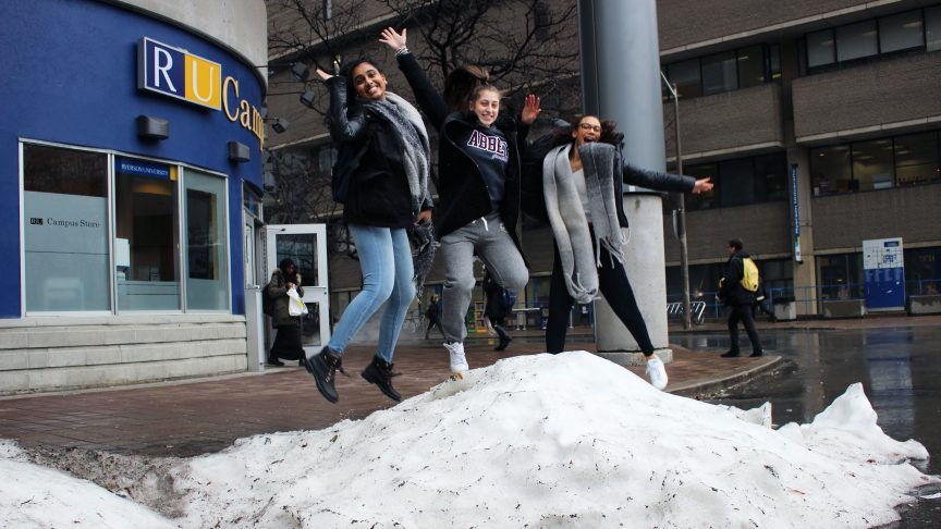 Three girls happily jump in a pile of snow on Gould Street.