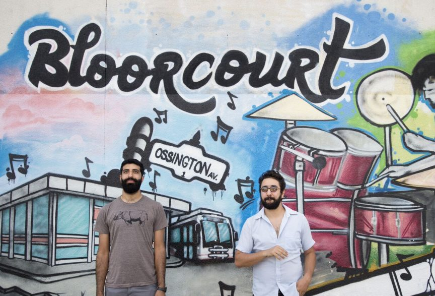 Uppal and Francouer stand in front of a Bloorcourt Mural