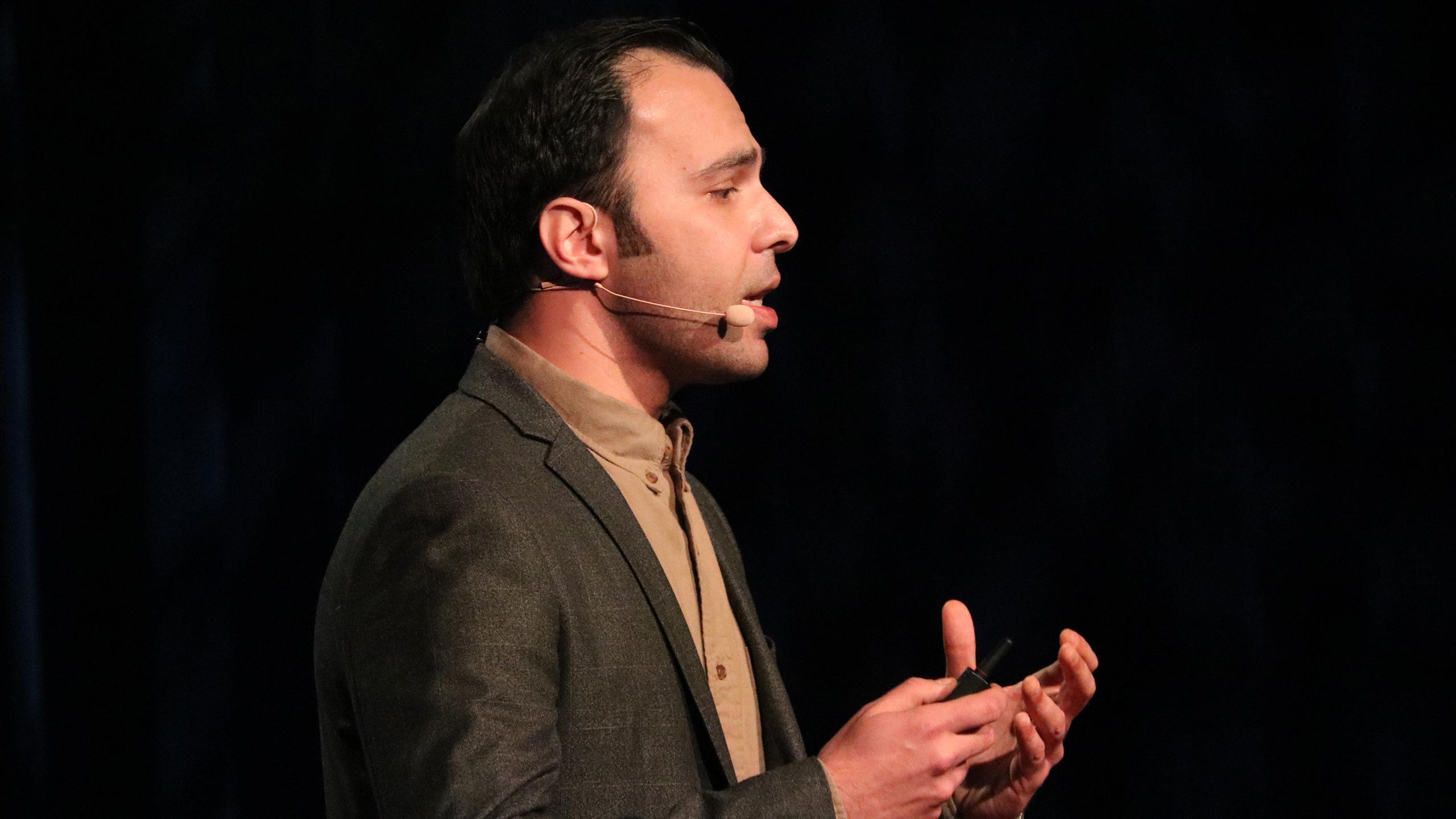 Ahmad Edilbi speaks on a stage.