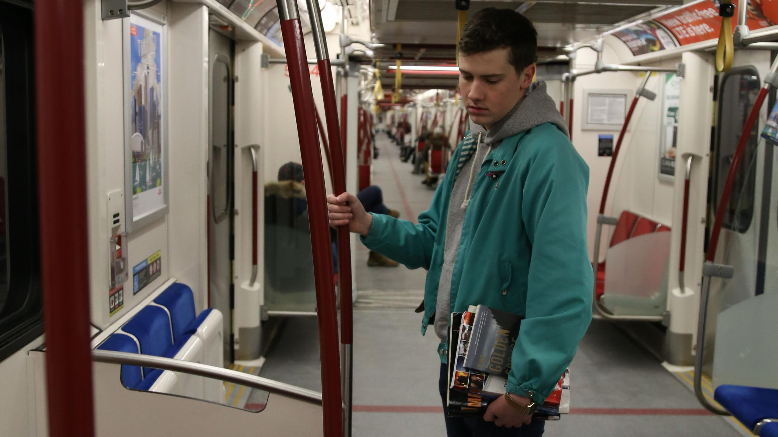 A student commuter looks exhausted on a subway car