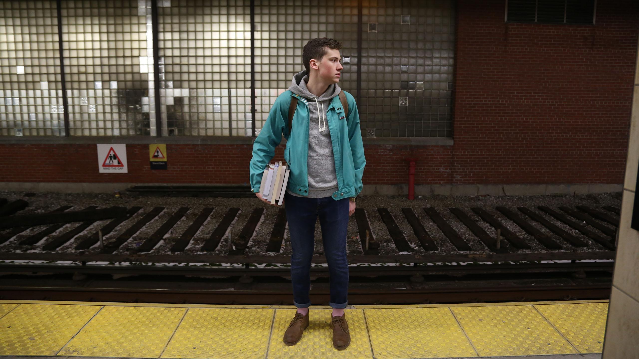 A student commuter stands on a platform