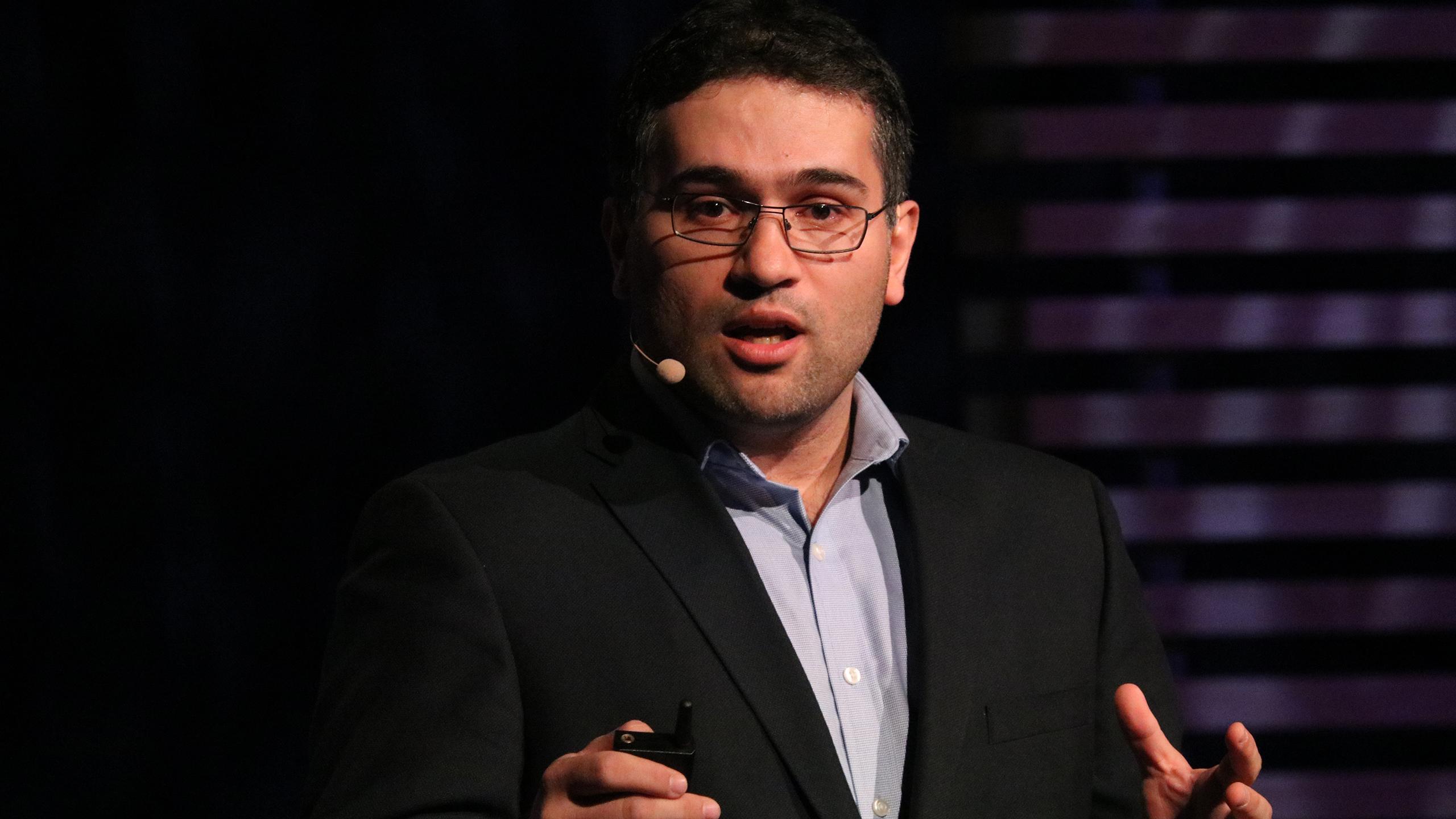 Ebrahim Bagheri speaks on a stage.