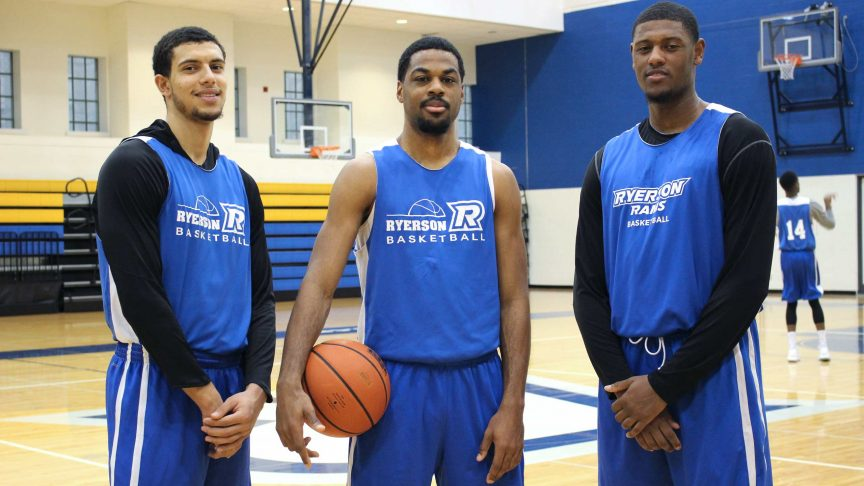Three Ryerson Basketball team captains stand on the court