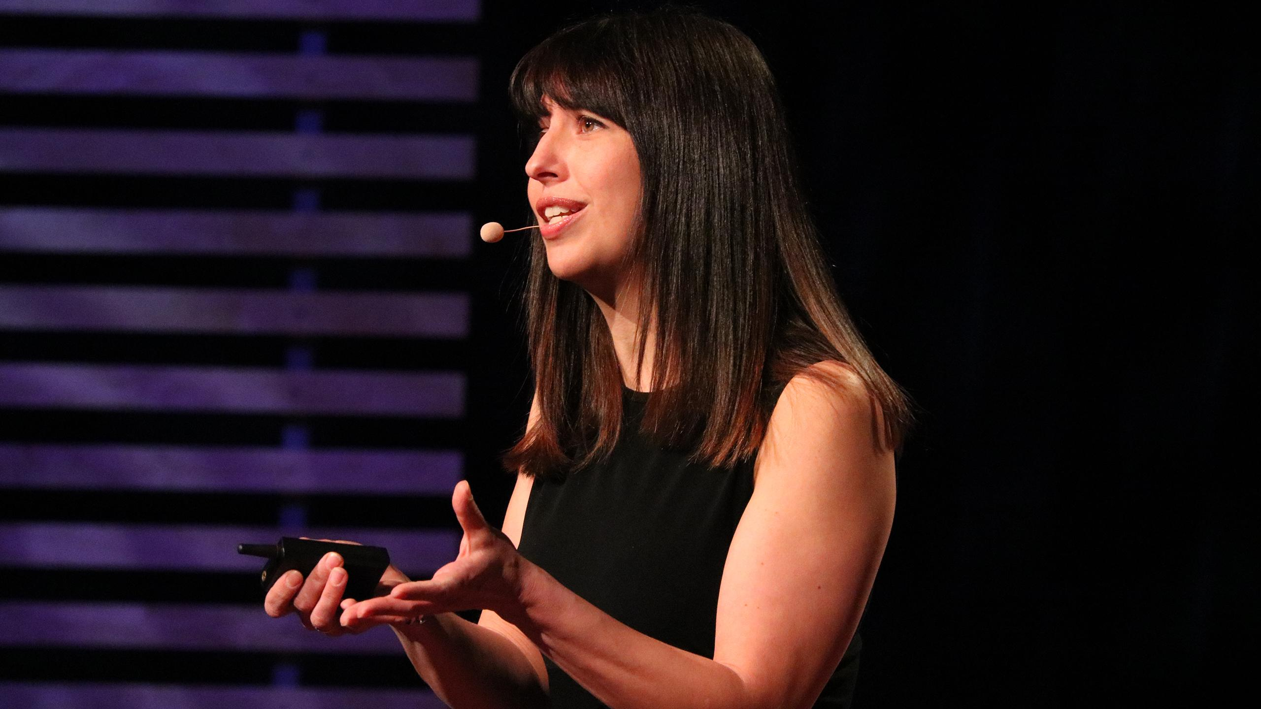 Laurie Petrou speaks on a stage.