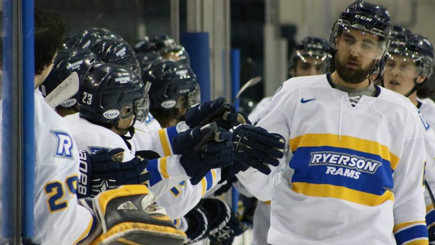 The Ryerson men's hockey players high five at the bench.