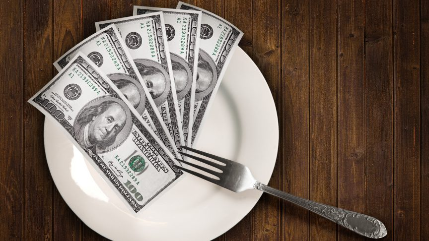 A stack of money sits on a dinner plate with a fork.