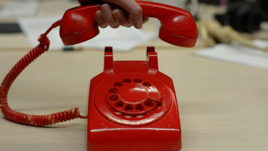 A red old style phone with a chord and dial.