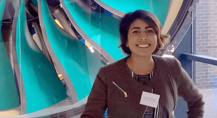 Priyanka Dhopade stands in front of a jet engine.