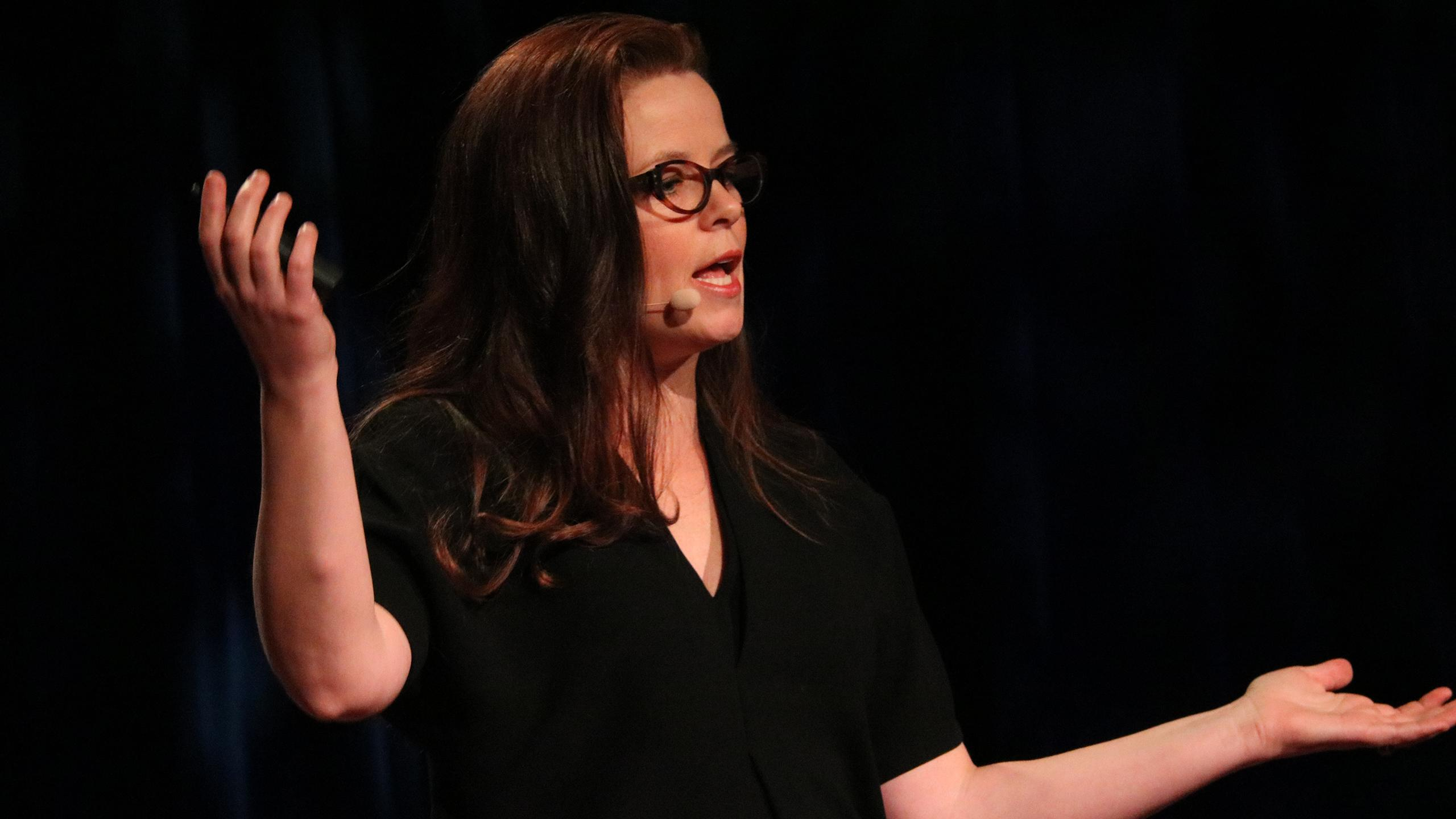 Shelagh McCartney speaks on a stage, her arms outstretched.