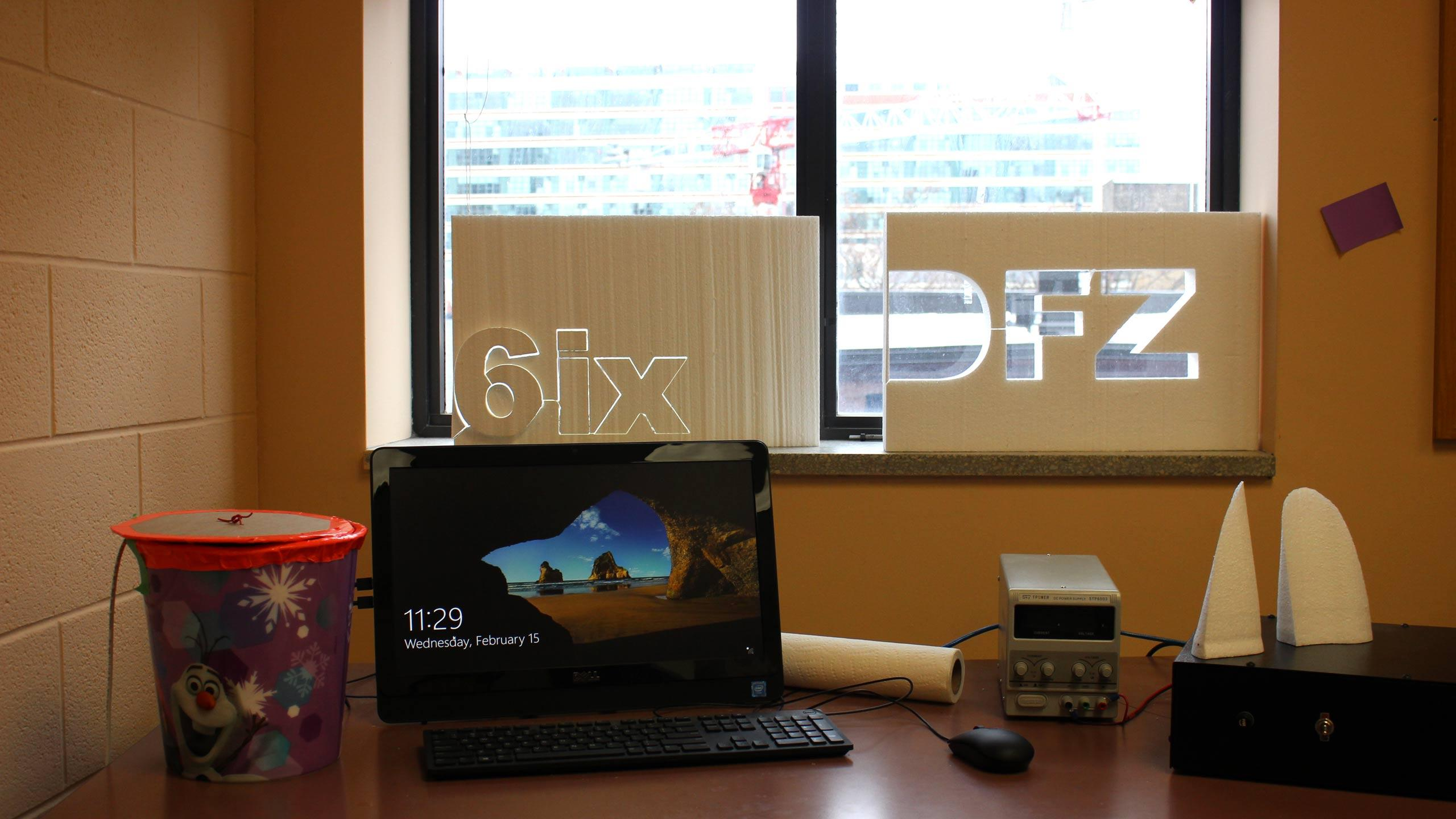 "Inside the DMZ space, there sits a laptop on a desk and in the window reads the words ""6ix"""