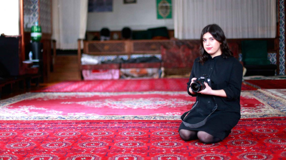 Photo of Alia Youssef kneeling with a camera