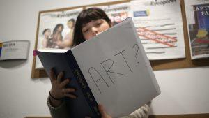 Somebody with an open book. The cover of the book reads: Art?