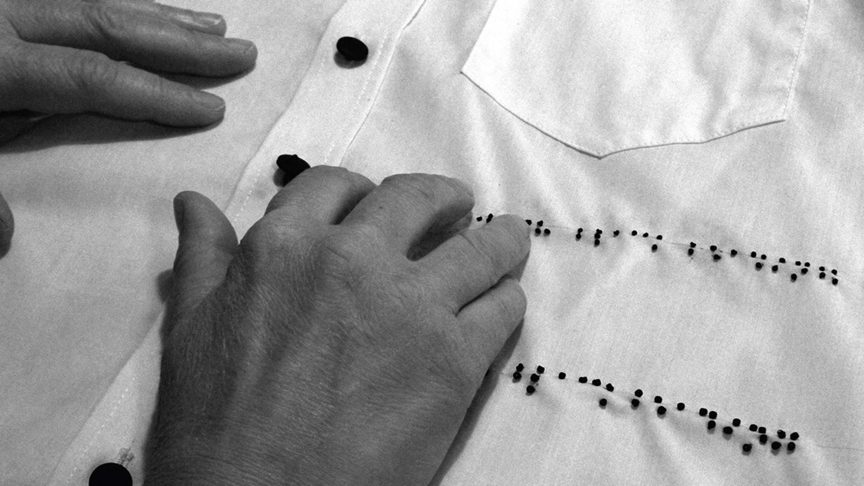 Hands reading braille on the front of a collared shirt