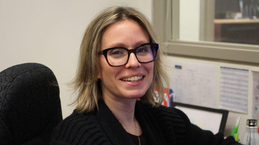 Caroline Konrad smiles at the camera. She's seated at her desk.