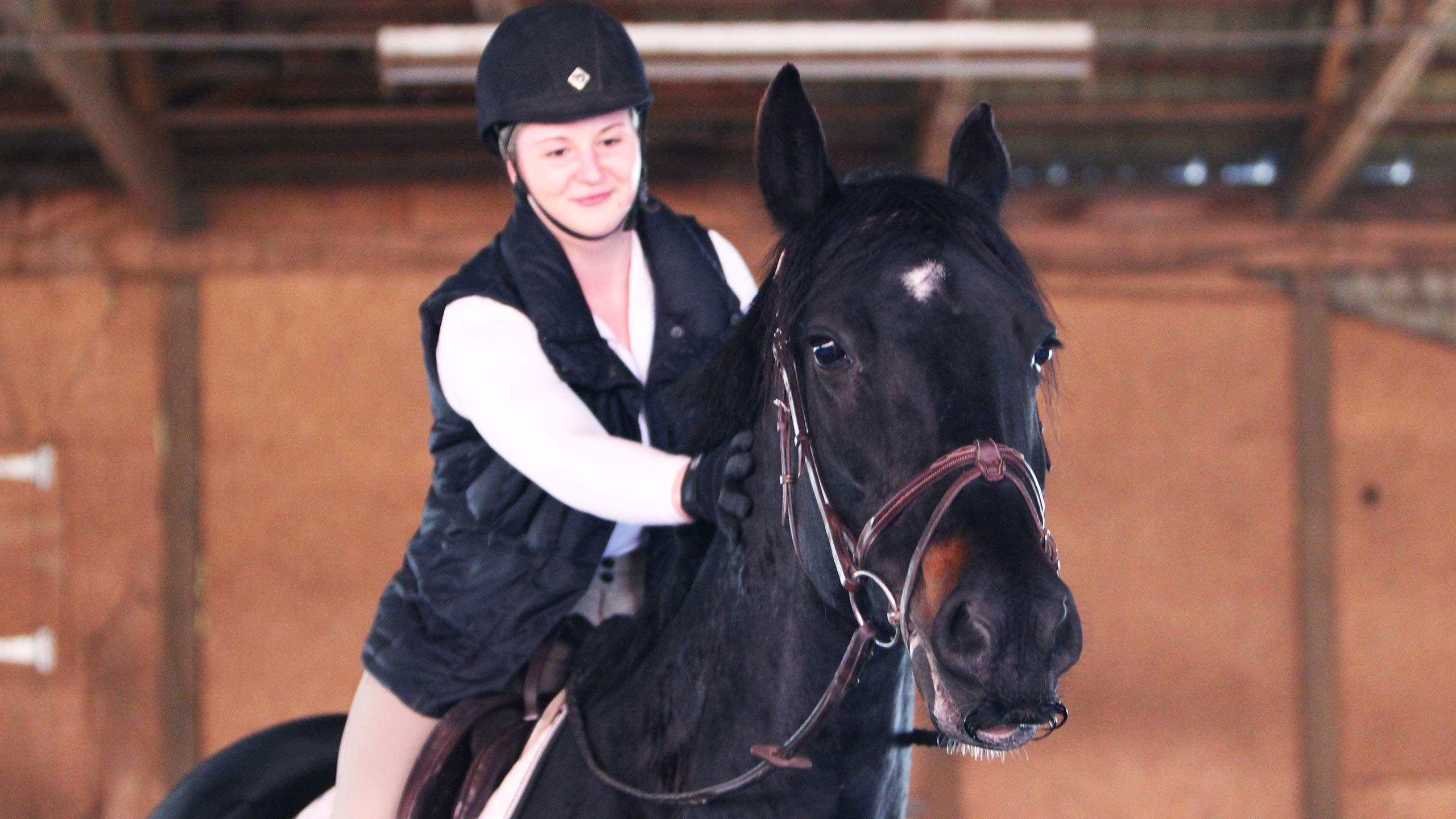 Katie stroking her horse, Onyx