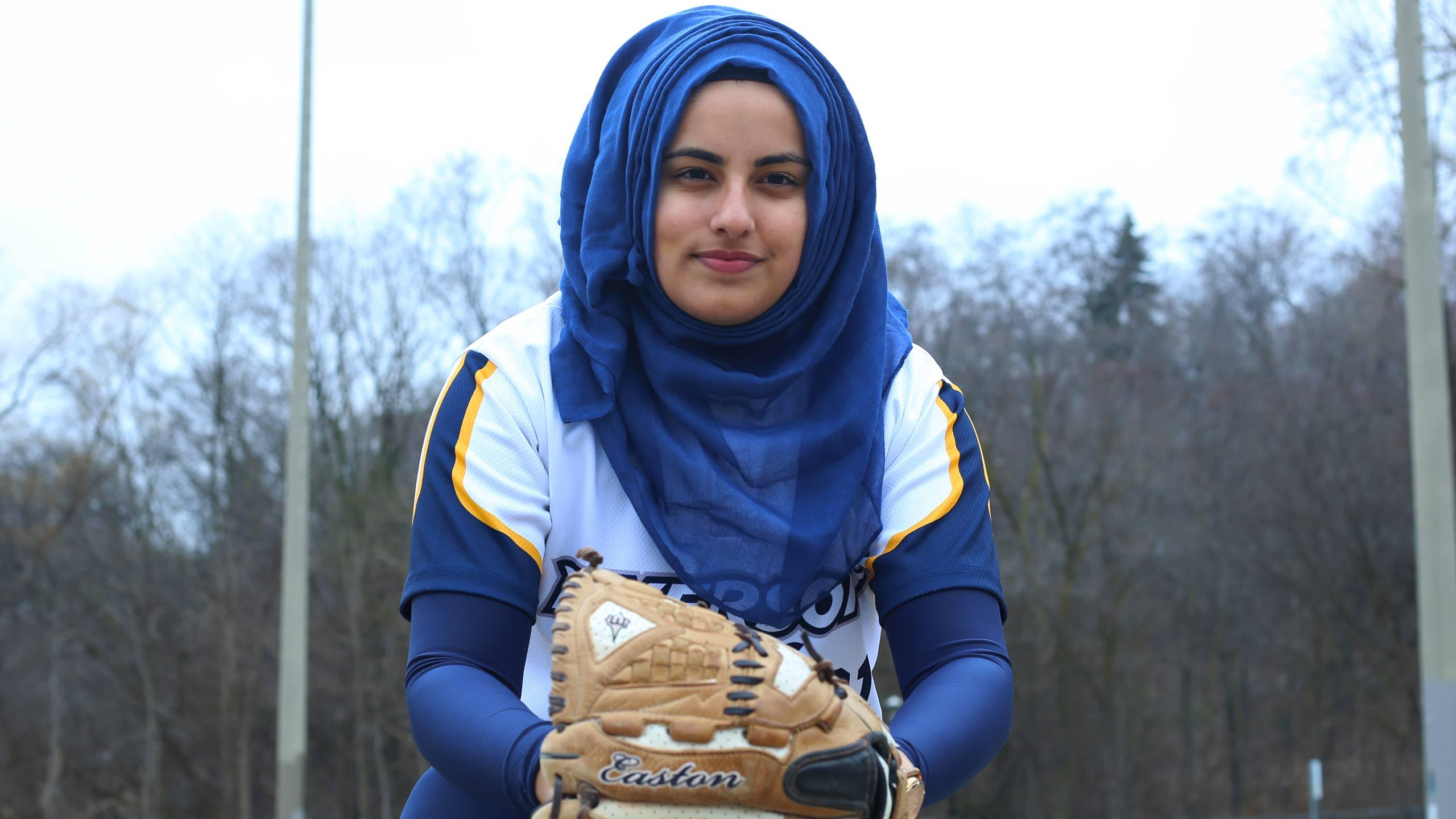 Azra Jessa at a baseball diamond with her glove.