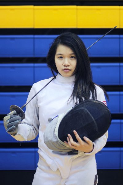Fencer posing holding her helmet and her sword