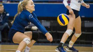 A volleyball player prepares to bump a ball