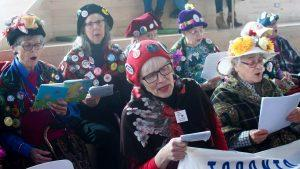 A group of ladies reading from pamphlets at the International Women's Day March