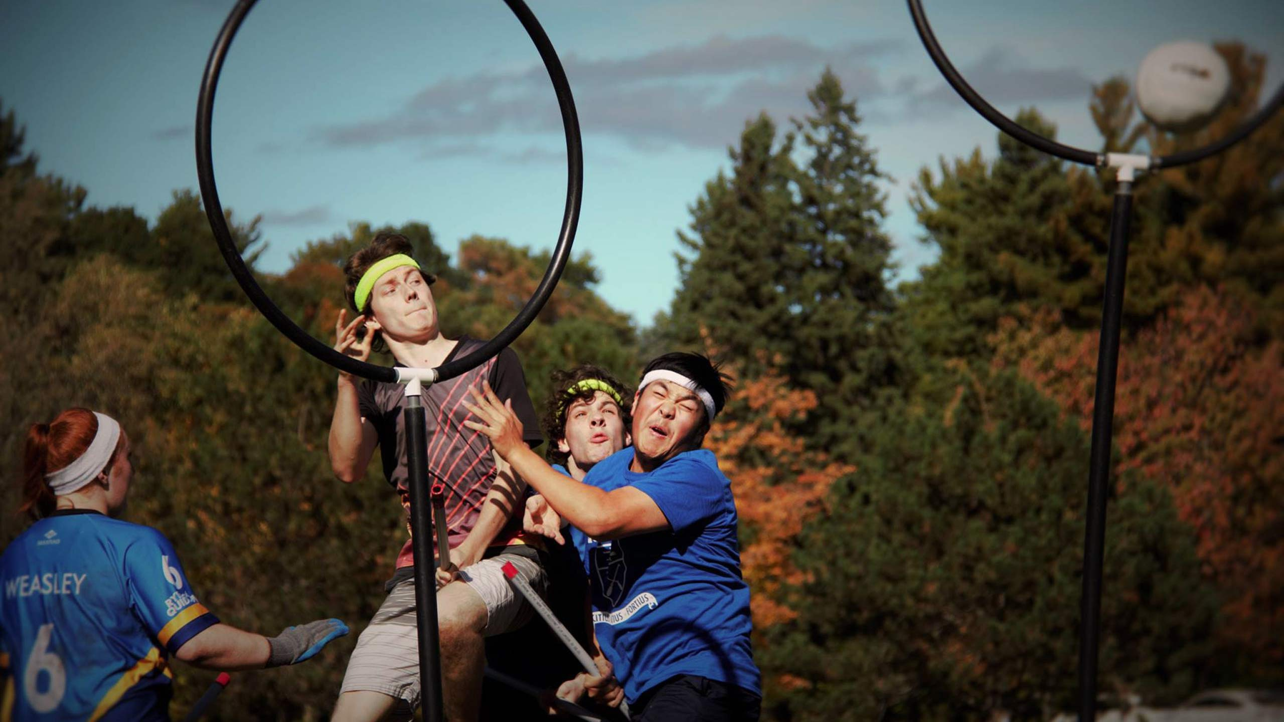 An epic shot of three quidditch players jumping up to hit a ball.