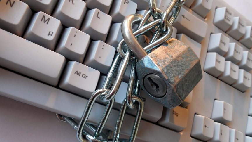 A padlock and chain wrapped around a keyboard.