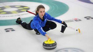 A Ryerson curler stretches along the ice in a pose