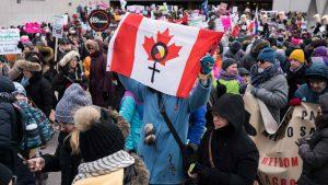 A canadian/native flag is held at the Women's March