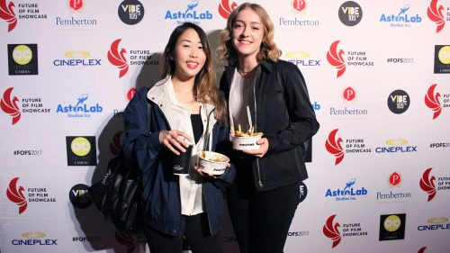 Sarah Quon (left) and Jessie Posthumus (right) eating poutine on the red carpet.