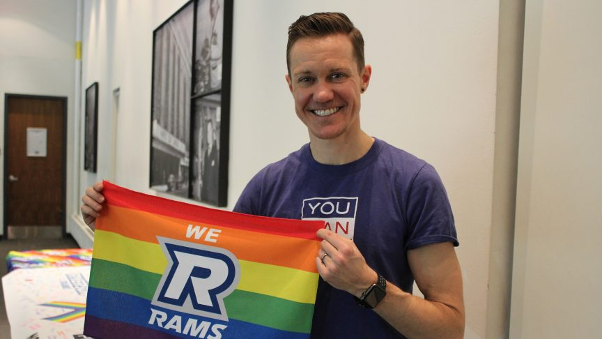 Chris Mosier poses with a we r rams rainbow flag