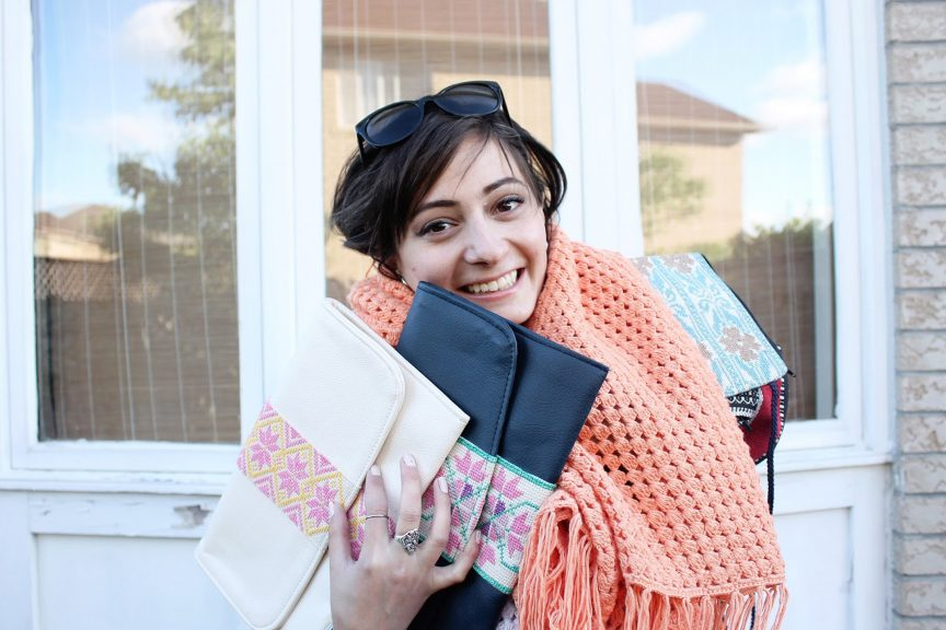 founder of the tight knit syria project holds knitted goods with a big smile on her face
