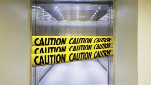 Elevator with caution tape across the open doors