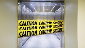 Elevator with caution tape across the open doors