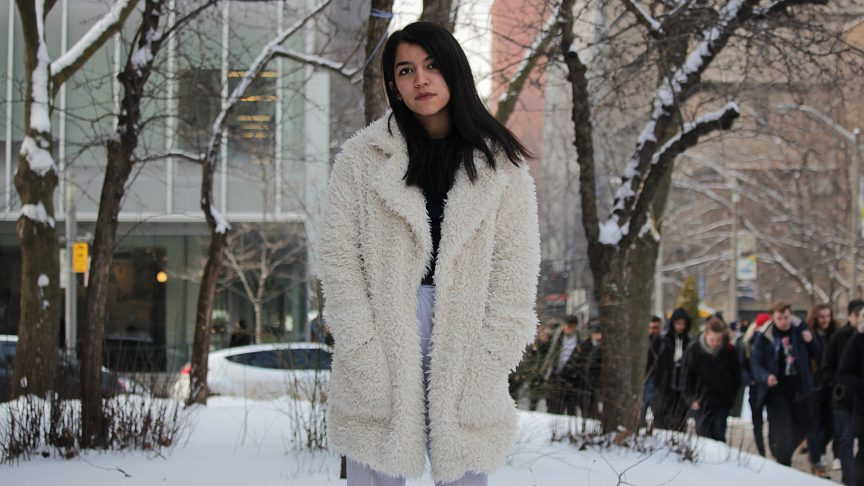 standing on Ryerson campus is a person wearing a fur coat. The background is a snowy winter wonderland.