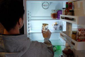 A student looks into an empty fridge