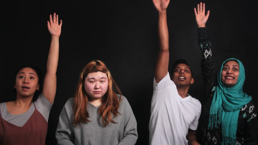 Three students enthusiastically raise their hands as one of their classmates looks sad that they're not participating