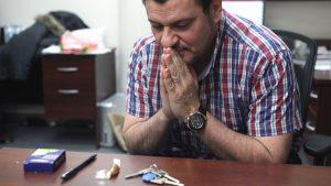 Dr.Majed, hands folded in prayer towards his tools of teaching. Keys, a candy, a pen and a box of staples.