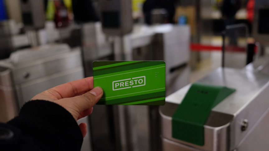 An arm holds a Presto card up in front of a fare gate