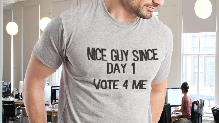 "Man wearing shirt that reads ""Nice guy since day one, vote for me"""